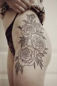 стильная татуировка с цветами на бедре